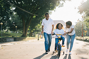 child with parents riding bike