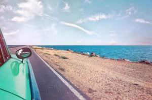 sea green car on blacktop by beach